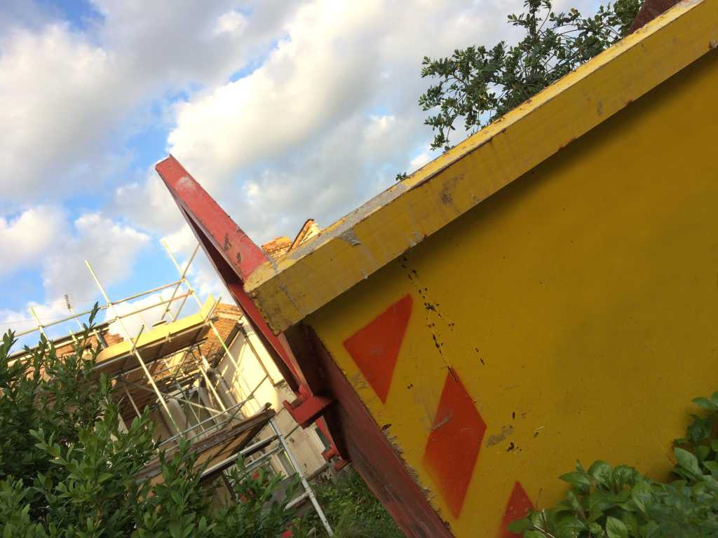 Yellow skip in front of construction site